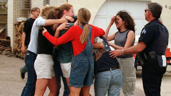 """SHOOTINGRTRO9XJ21 Apr. 1999Littleton, USAColumbine high school students and friends rush and hug a friend who had just escaped from inside the high school where gunmen opened fire on terrified students, possibly killing up to 23 people before taking their own lives, police said. Jeff Stone, sheriff of Jefferson County, said the gunmen, students at the school, were found dead in the library on what he called a """"suicide mission."""