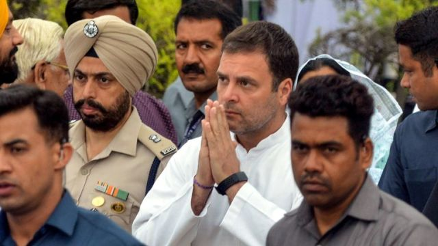 Indian National Congress party president Rahul Gandhi (C) after laying a wreath