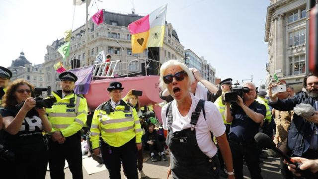 British actress Emma Thompson (C) gestures as police surround the pink boat being used as a stage by climate change activists as they occupy the road junction at Oxford Circus in central London on April 19, 2019 during the fifth day of an environmental protest by the Extinction Rebellion group