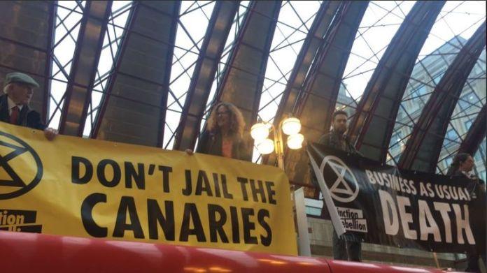 Protesters climb onto a DLR train at Canary Wharf