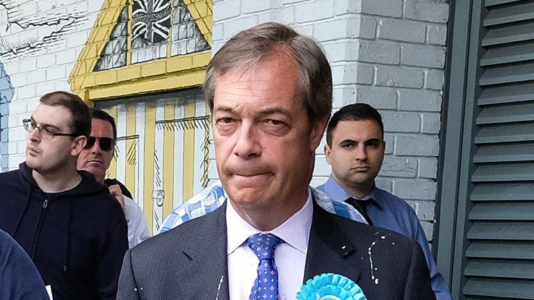 Nigel Farage is escorted to a car after having milkshake thrown over him