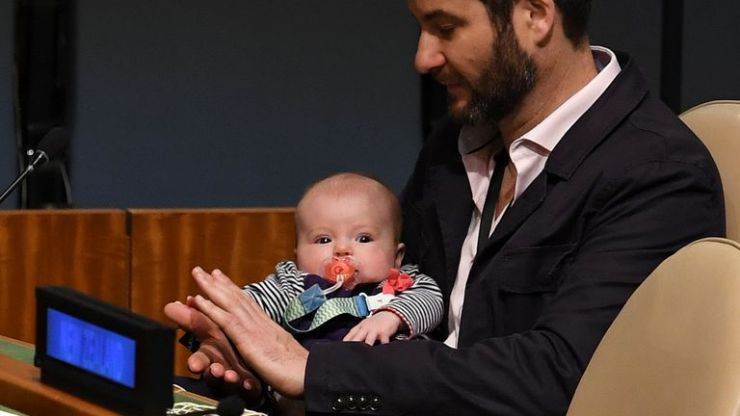 Clarke Gayford (C) claps holding his daughter Neve Te Aroha Ardern Gayford, as his partner Jacinda Ardern, Prime Minister and Minister for Arts, Culture and Heritage, and National Security and Intelligence of New Zealand speaks during the Nelson Mandela Peace Summit September 24, 2018, one day before the start of the General Debate of the 73rd session of the General Assembly at the United Nations in New York