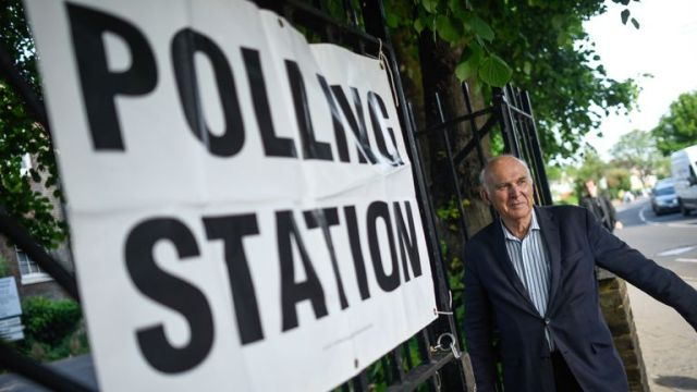 Vince Cable arrives at a polling station to vote in European Parliament elections