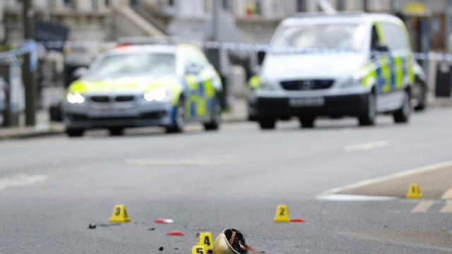 RETRANSMITTING WITH ADDED PIXELATION DUE TO GRAPHIC CONTENT. A helmet lies on the ground at a scene in Battersea, south-west London, where woman has died after being struck by a lorry while riding a scooter.
