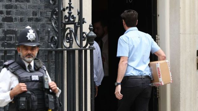 A package containing a digital countdown clock is carried in to 10 Downing Street in London.