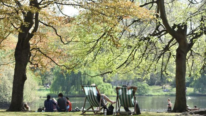 People relax and enjoy the sunshine in deck chairs by the lake in St James's Park on April 22, 2019 in London, England