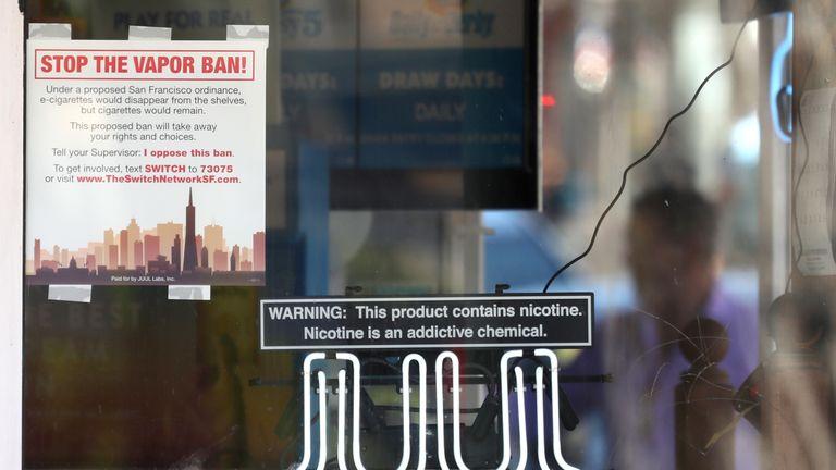 Une enseigne au néon annonçant des cigarettes électroniques Juul est exposée dans une vitrine d'un magasin de tabac le 25 juin 2019 à San Francisco, en Californie. Le conseil de surveillance de San Francisco a voté à l'unanimité, 11-0, d'être la première ville des États-Unis à interdire les cigarettes électroniques, les capsules de nicotine et les dispositifs non approuvés par la Food and Drug Administration.