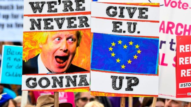 Demonstrators hold placards and EU and Union flags as they take part in a march by the People's Vote organisation