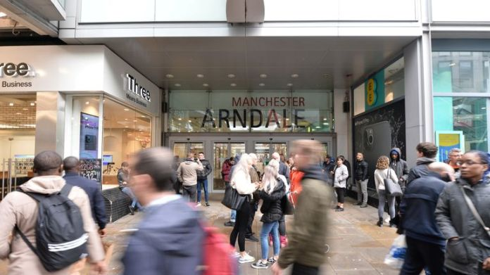 People walk in front of the entrance to the Arndale Shopping Center