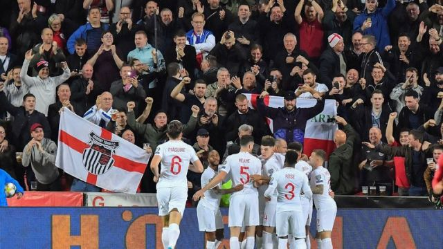 England's forward Harry Kane (hidden) celebrates scoring the opening goal with his teammates in front of their fans during the UEFA Euro 2020 qualifier Group A football match Czech Republic v England at the Sinobo Arena on October 11, 2019. (Photo by JOE KLAMAR / AFP) (Photo by JOE KLAMAR/AFP via Getty Images)