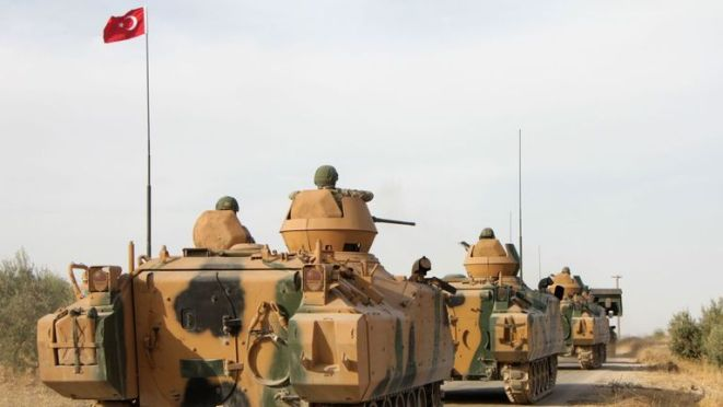 Turkish soldiers are trasported in armoured personnel carriers through the town of Tukhar, north of Syria's northern city of Manbij