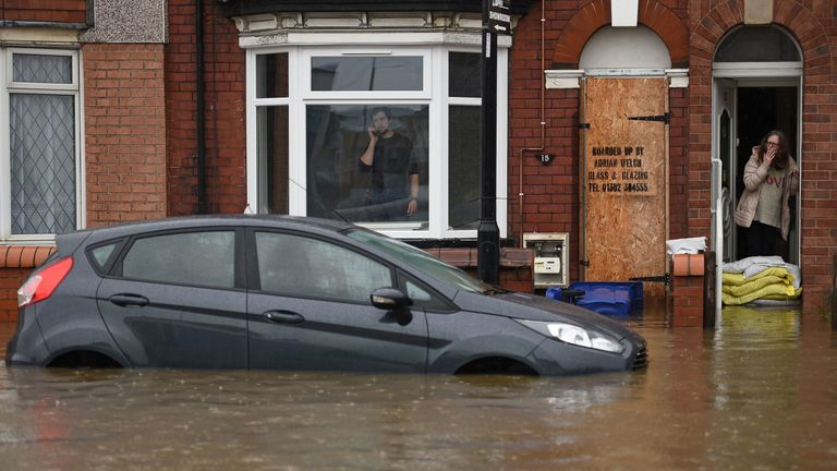 A woman stands behind sandbags in Doncaster