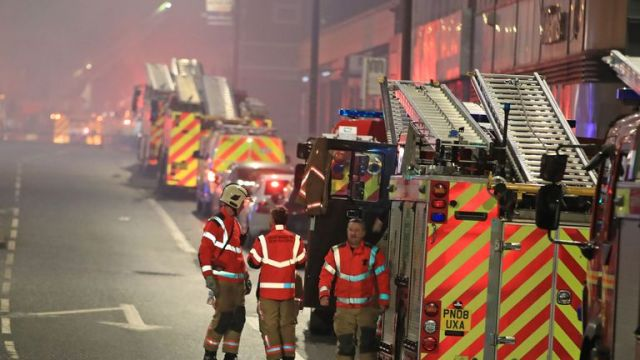 Firefighters at the scene after a fire on the top floors of a building on Bradshawgate in Bolton