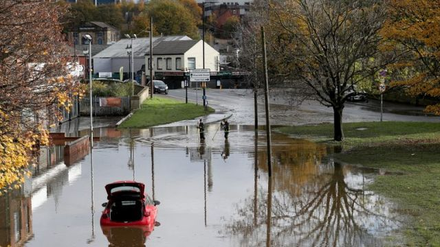 A car remains stranded in a flooded street in central Rotherham