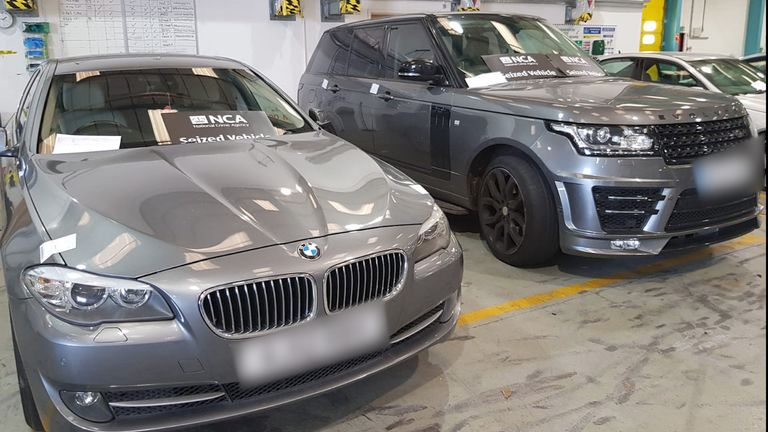 A BMW 5 series and a Range Rover Vogue after they were both recovered by officers