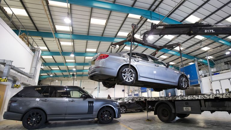 A BMW 5 series is lowered next to a Range Rover Vogue after they were both recovered by officers