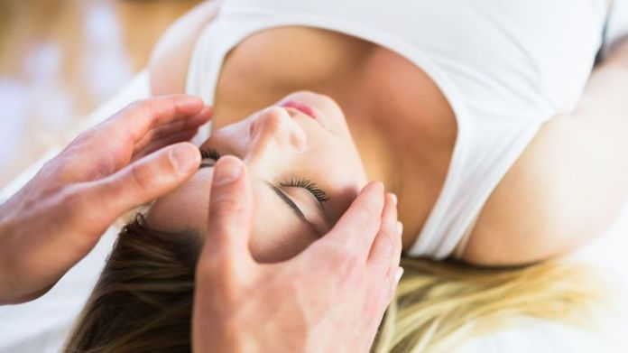 Reiki, a form of alternative medicine, uses a palm healing technique on patients