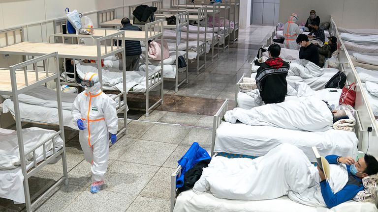Medical workers in protective suits attend to patients at the Wuhan International Conference and Exhibition Centre, which has been converted into a makeshift hospital