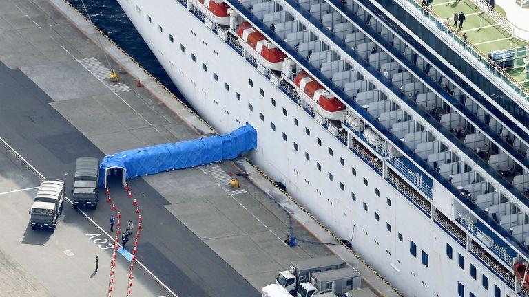 Passengers can be seen disembarking the Diamond Princess