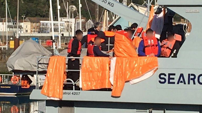 Migrants are brought ashore on the Border Force vessel Searcher in Dover