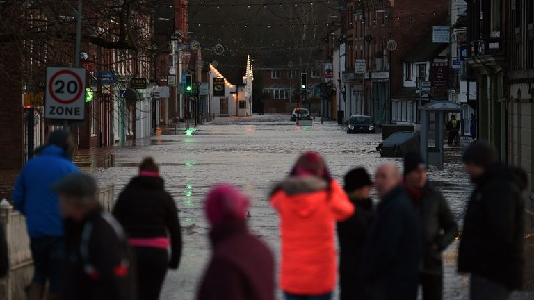 People look at flood water in a flooded street in Tenbury Wells, after the River Teme burst its banks in western England, on February 16, 2020, after Storm Dennis caused flooding across large swathes of Britain