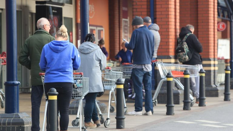 People queue at a Sainsbury's supermarket at Colton, on the outskirts of Leeds, the day after Prime Minister Boris Johnson put the UK in lockdown to help curb the spread of the coronavirus.