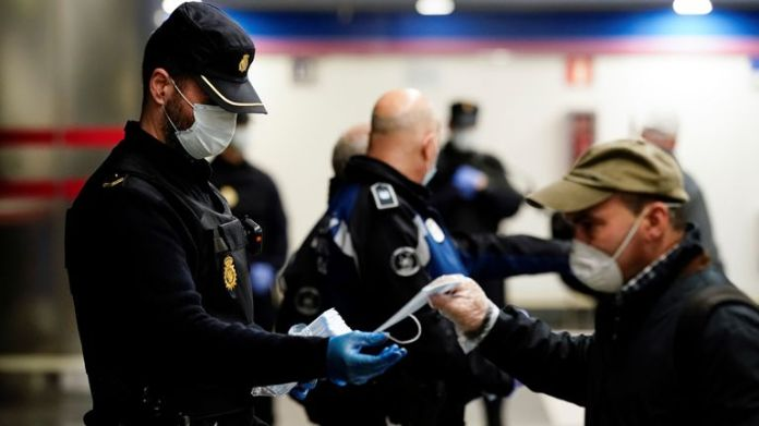 A police officer gives out free protective face masks at a metro station