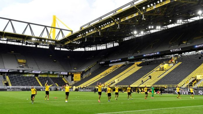 Dortmund players cheer after 4-0 win, but celebrate in nearly empty stadium