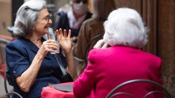 Women are seen enjoying a drink al fresco as Italy began easing lockdown on 18 March