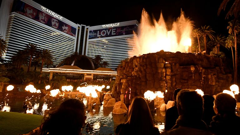 """LAS VEGAS, NEVADA - MARCH 14: Building wraps for the """"The Beatles LOVE by Cirque du Soleil"""" show are shown on the exterior of The Mirage Hotel & Casino as visitors watch the resort's volcano attraction as the coronavirus continues to spread across the United States"""