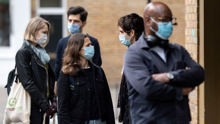 Members of the public in face masks queue 2 meters apart outside a shop in East London