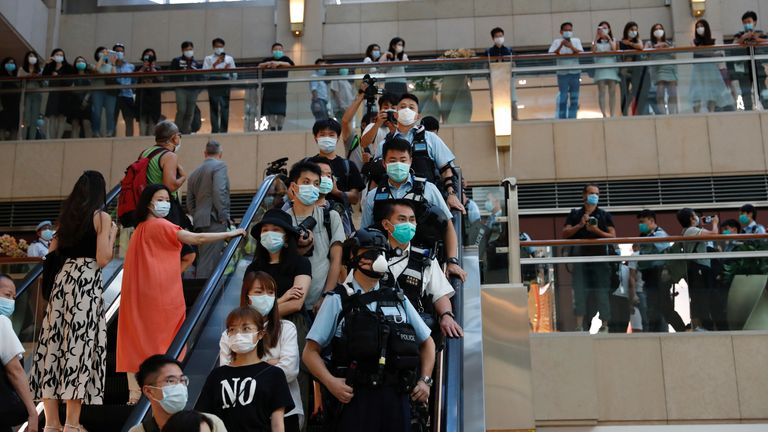Riot police were deployed to an upmarket shopping centre in Hong Kong as peaceful pro-democracy protesters carried out a minute's silence