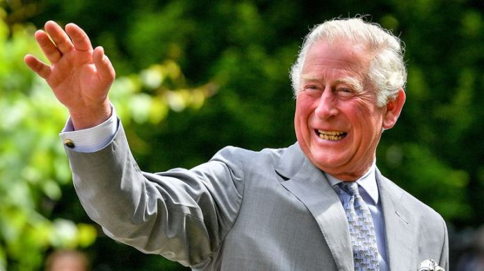 Charles waves to onlookers who came out to greet him