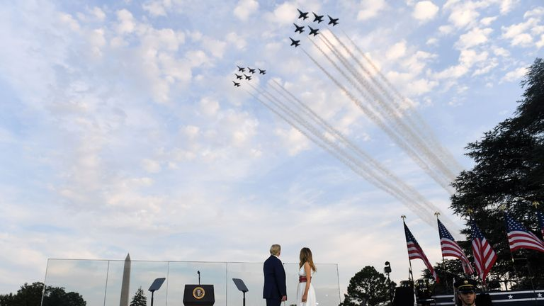 """US President Donald Trump and First Lady Melania Trump watch as Thunderbirds and Blue Angels aircrafts flyover during the 2020 """"Salute to America"""" event in honor of Independence Day on the South Lawn of the White House in Washington, DC, July 4, 2020. (Photo by SAUL LOEB / AFP) (Photo by SAUL LOEB/AFP via Getty Images)"""