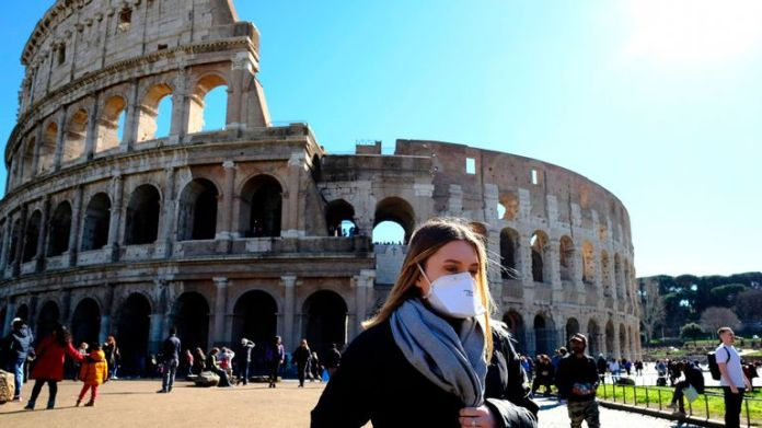 Tourist wearing a protective breathing mask visits outside the Colosseo monument (Colosseum, Coliseum) in downtown Rome on February 28, 2020 amid fears of the Covid-19 epidemic.  - Since February 23, more than 50,000 people have been confined in 10 cities in Lombardy and one in Veneto - a drastic step taken to stop the spread of the new coronavirus, which has infected some 400 people in Italy, mainly in the north.  (Photo by Andreas SOLARO / AFP) (Photo by ANDREAS SOLARO / AFP via Getty Images)