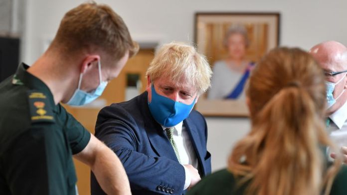 Prime Minister Boris Johnson (2L), wearing a face mask or blanket due to the COVID-19 pandemic, elbows a paramedic as he travels to the headquarters of the London Ambulance Service NHS Trust in central London on July 13, 2020. (Photo by Ben STANSALL / POOL / AFP) (Photo by BEN STANSALL / POOL / AFP via Getty Images)