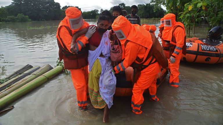 An unwell woman is rescued from the floods in Pathsala, Assam