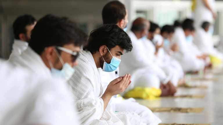 A pilgrim wearing a face mask prays at the Grand Mosque in Mecca