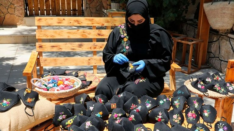 A women near Hebron makes face masks - people in the West Bank have also been told to stay home