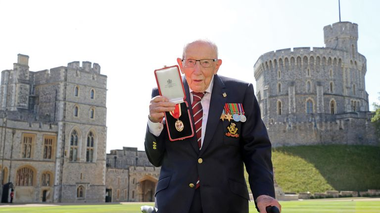 Sir Tom proudly shows off his  medal