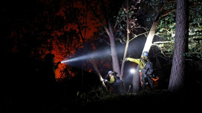Crews clear brush in the path of a fire near Lake Oroville, California