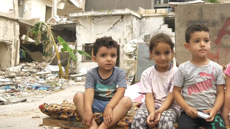 A Syrian refugee family sit in the ruins of their building, destroyed by the explosion in Beirut