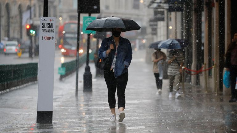 A pedestrian wearing PPE (personal protective equipment), of a face mask or covering as a precautionary measure against COVID-19, shelters under an umbrella they are caught in a downpour of rain on Oxford Street in London on June 17, 2020, as lockdown restrictions imposed to stem the spread of the novel coronavirus continue to be relaxed. - Britain's annual inflation rate slid to 0.5 percent in May, the lowest level in four years, as the country's coronavirus lockdown dampens prices, official da