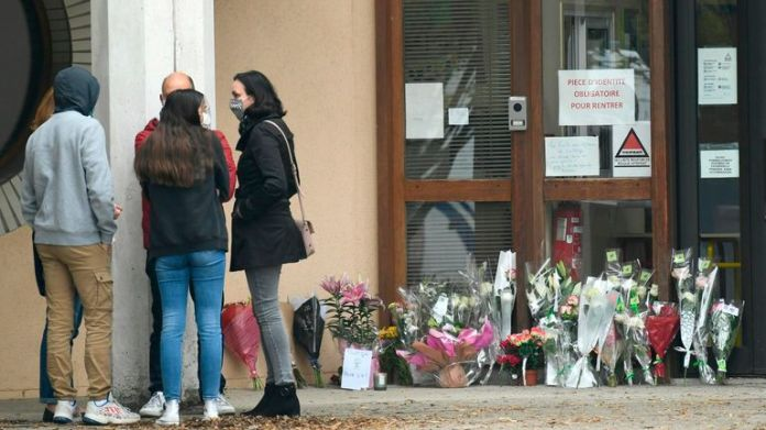 Flowers were laid at the entrance to a college in Conflans-Sainte-Honorine, 30 km northwest of Paris, on October 17, 2020, after a teacher was beheaded by an attacker shot dead by police .