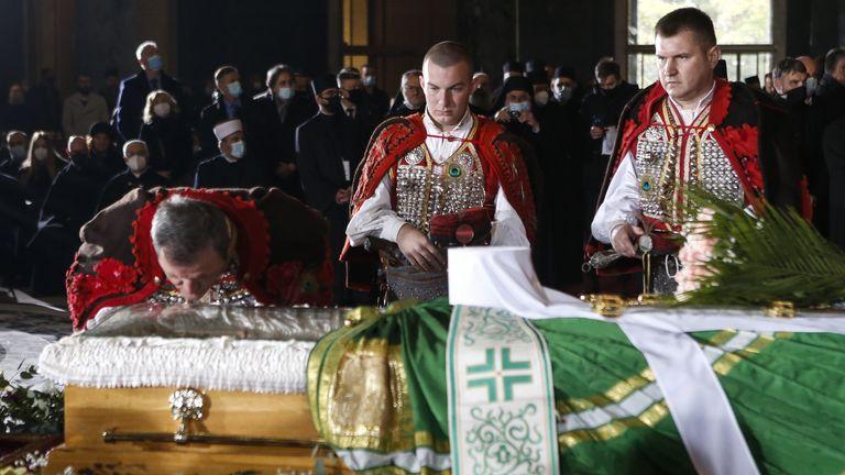 Мужчина целует гроб Патриарха Иринея во время похоронной процессии в храме Святого Саввы.