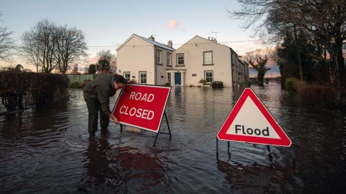 Gabrielle Burns-Smith erects a road closed sign on Warrington Lane on the outskirts of Lymm in Cheshire as Storm Christoph causes widespread flooding across the UK. Picture date: Thursday January 21, 2021.