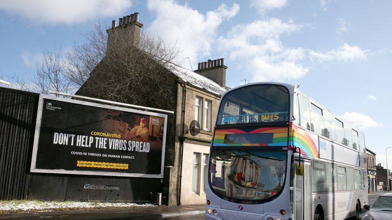 A bus decorated with a rainbow and NHS stickers passes a Coronavirus related advert on a billboard in Falkirk, Central Scotland, where lockdown measures introduced on January 5 for mainland Scotland remain in effect until at least the end of February. Picture date: Monday February 8, 2021.