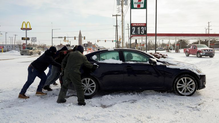 People in Oklahome try to free a stuck motorist during record-breaking freezing weather.