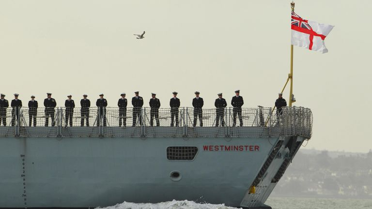 Crewmembers of the Royal Navy's Type 23 frigate HMS Westminster line the deck as they set sail from Portsmouth Harbor on a seven month mission to maintain security in the Middle East.