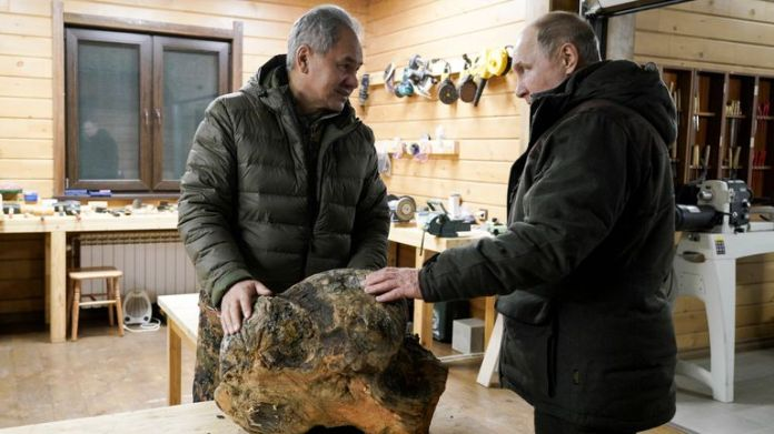Russian Defense Minister Sergei Shoigu, left, and Russian President Vladimir Putin talk to each other and look at a piece of wood being made in Sergei Shoigu's workshop in a taiga forest in Russia's Siberia region.